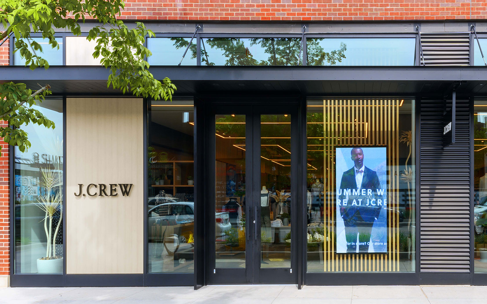 Blackened steel and glass combine with wood veneer and brick to create the facade of J Crew's newly designed store.