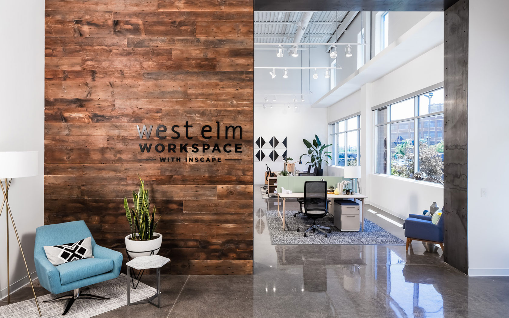 Polished stone floors, a wood-paneled wall, and white accents create the entry to the West Elm Workspace store.