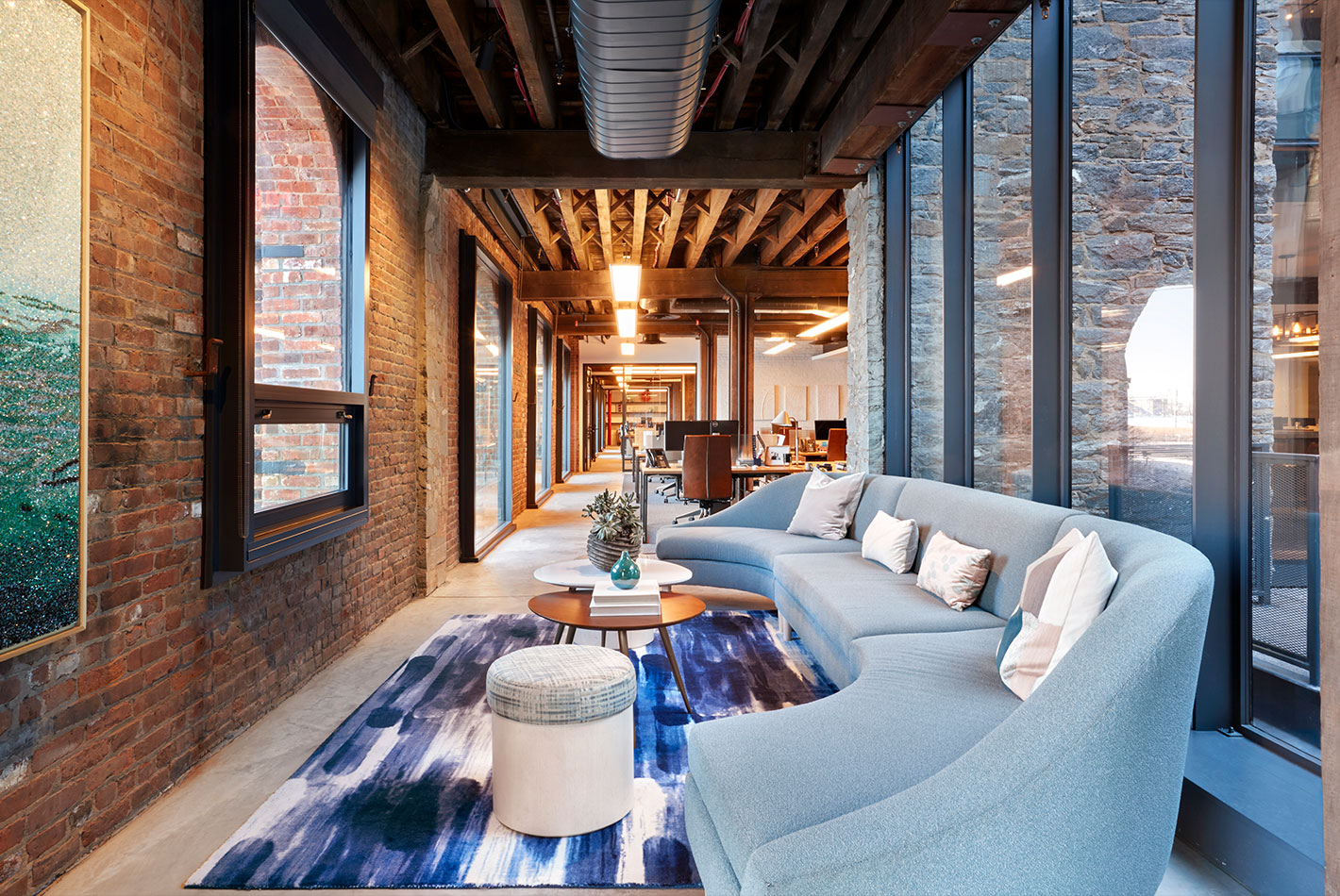 A long corridor with arched windows facing the Manhattan Bridge is used for multiple seating areas perfect for casual meetings at West Elm Headquarters.
