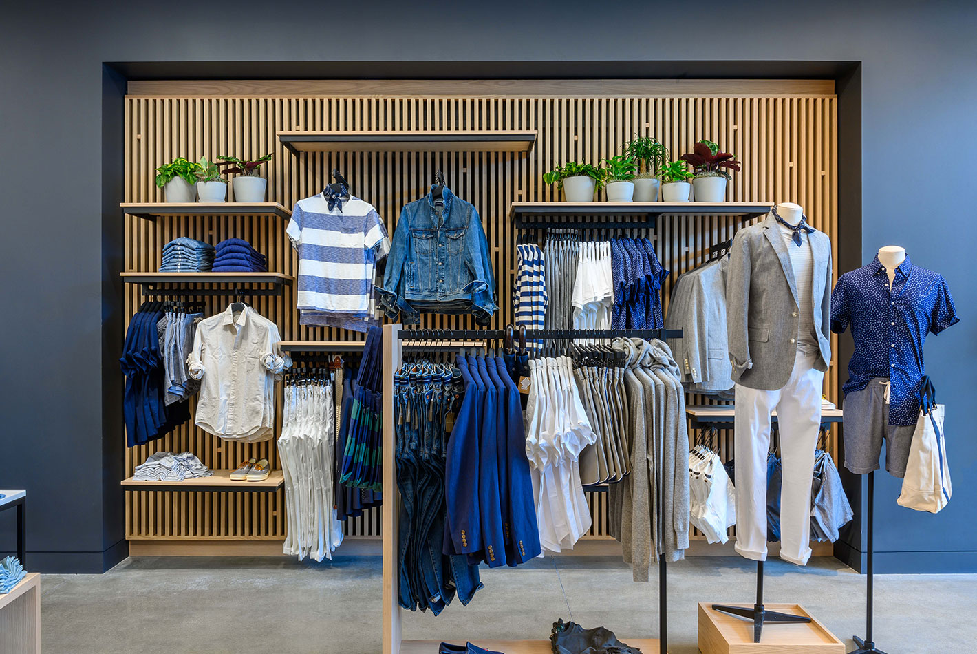 Color coordinated blue and white men's clothing is arranged near a wood-slatted wall, over-painted with blue-gray paint at J Crew