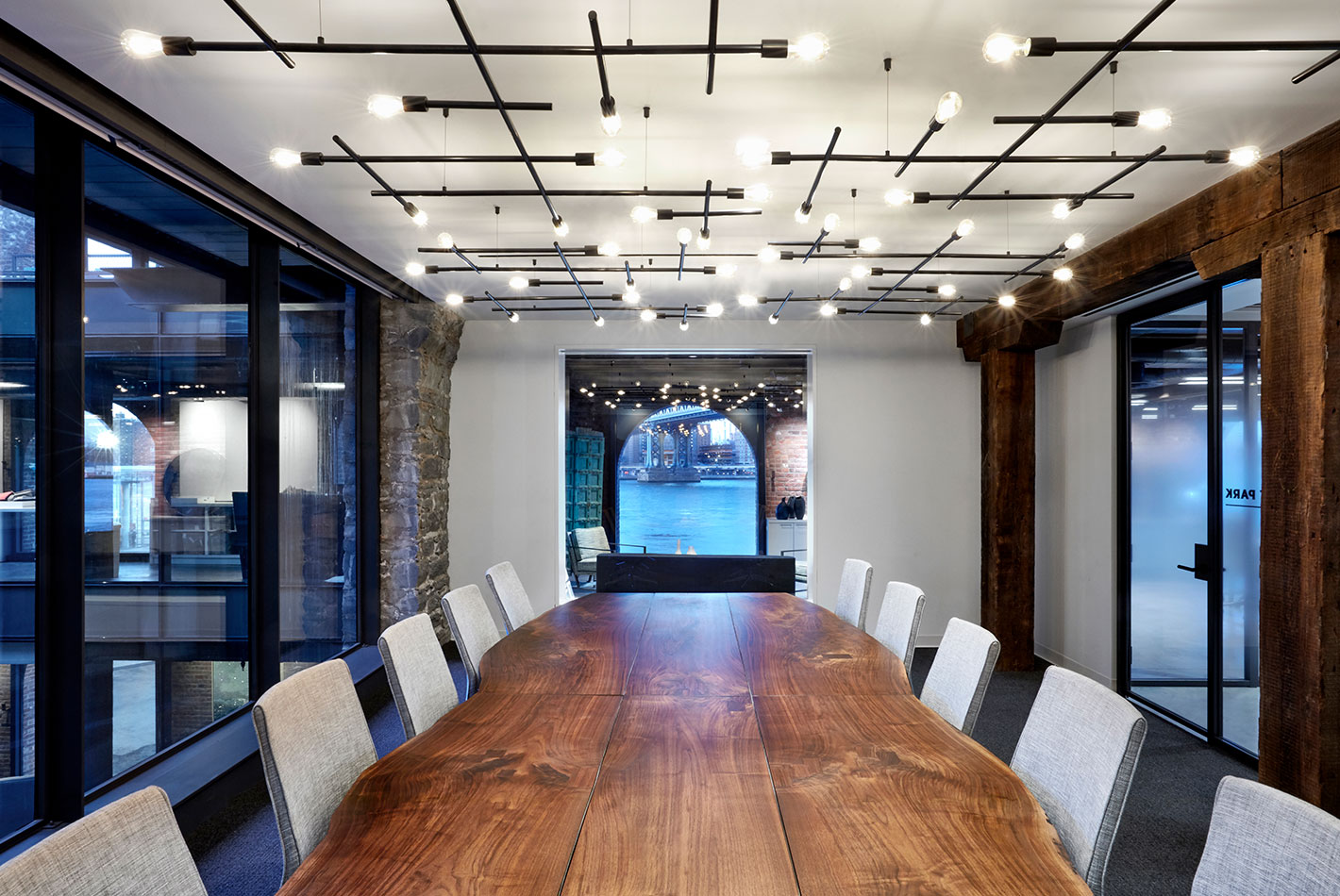 A live-edge wooden table runs through the center of the conference room at West Elm Headquarters. The ceiling light fixtures create a grid pattern.